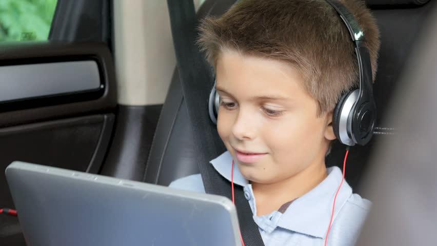 dziecko ogląda bajkę na laptopie podczas podróży w samochodzie