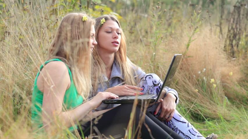 dziewczyny oglądają telewizję na laptopie na łące