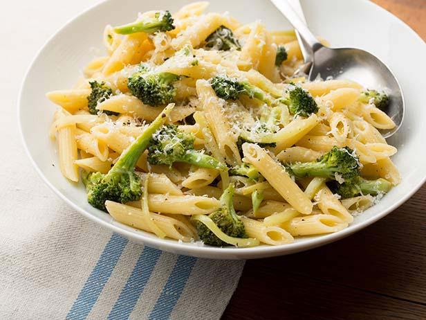 talerz z penne brokułami mascarpone posypane żółtym serem na obrusie z niebieskim bieżnikiem
