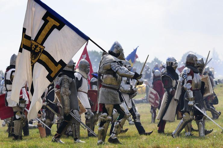 grunwald - inscenizacja bitwy, zdjęcie rycerzy z mieczami i flagami