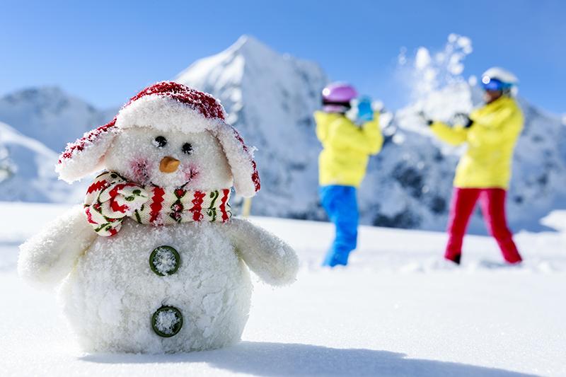 bałwanek w czapeczce i szaliczku a w tle dzieci bawiące się śniegiem