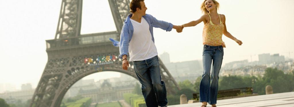 szczęśliwa para trzymająca się za ręce pod wieżą Eiffla w Paryż wycieczka