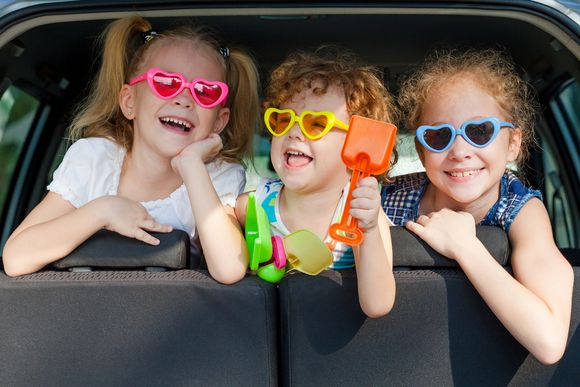 wesołe dzieci w kolorowych przeciwsłonecznych w kształcie serca okularach siedzą w samochodzie
